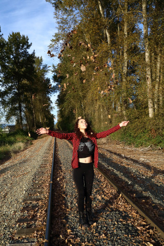 Senior photo with fall leaves on railroad tracks in Marysville, WA