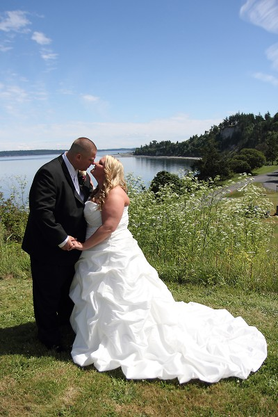 Bride and groom kiss on the cliffs of Fort Worden State Park