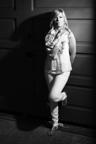 Model leaning on door with high contrast lighting